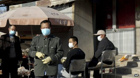 Chinese men stand guard in front of the house of a seven-year-old H7N9 bird flu patient in Gucheng village on the outskirts of Beijing