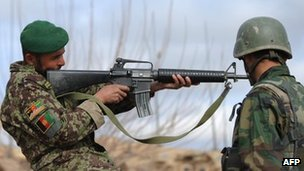 An Afghanistan National Army soldier checks a weapon in Helmand