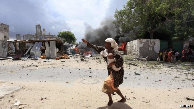 A Somali woman runs to safety near the scene of a blast