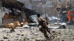 A Somali soldier runs near the scene of the attack