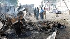 Somali soldiers look at the wreckage of a car bomb used in the attack