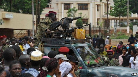 Seleka rebels sitting on a pick-up truck next to machine-guns as a crowd gathers in Bangui on 30 March 2013