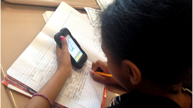 A schoolgirl using an iPod application to learn handwriting