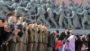 Military personnel salute as civilians bow to giant statues of the late North Korean leaders Kim Il-sung and his son, Kim Jong-il, unseen, in Pyongyang, North Korea, 15 April 2013