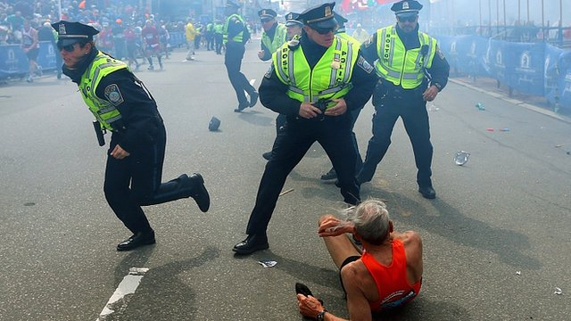 Bill Iffrig, 78, lies on the ground as police officers react to a second explosion at the finish line of the Boston Marathon
