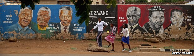 People walk past a mural of Nelson Mandela's timeline in Johannesburg