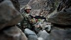 An Afghan Army soldier takes position on a road leading from Kabul to Jalalabad