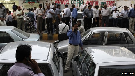 Office workers stand outside their buildings following an earthquake tremor in Karachi on 16 April 2013