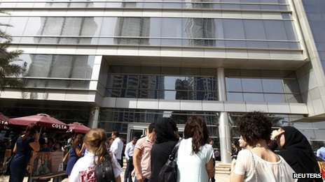 People wait outside after evacuating offices in Dubai Media City following earthquake tremors in Dubai April 16, 2013.