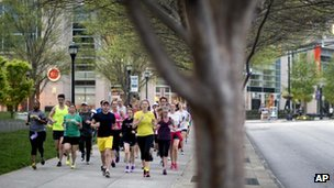 Runners jog along Peachtree Street as part of an organized moment of silence and memorial run to show solidarity with victims of the Boston Marathon bombing, in Atlanta, Georgia 16 April 2013