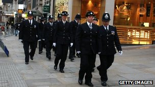 Police officers walk along the Strand