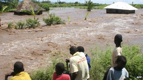 Residents of Kano plains look on 14 April 2013 at one of the homes that was submerged by floodwaters after the Nyando river burst its banks, displacing families in the area and forcing most to move to higher ground for safety