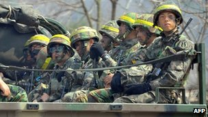 South Korean soldiers ride a military truck on a road in the border city of Paju on 17 April 2013
