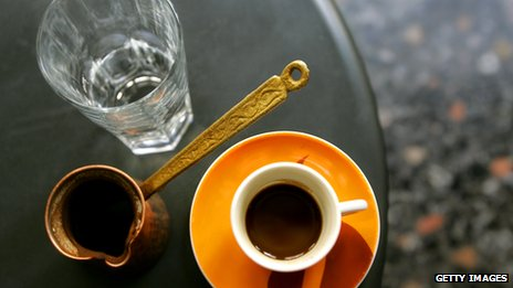 Greek coffee maker known as a briki, coffee in a cup, served with a glass of water