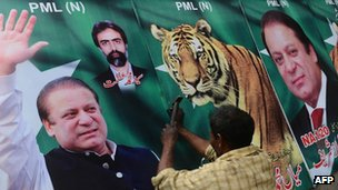 A Pakistani worker fixes billboards featuring photographs of Nawaz Sharif in Lahore (April 2013)