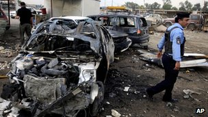 A policeman inspects the aftermath of a car bomb attack at a used cars dealers parking lot in Habibiya neighbourhood of eastern Baghdad, Iraq, Tuesday, April 16, 2013.