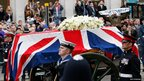 A Union flag draped coffin is carried on a gun carriage drawn by the King's Troop Royal Artillery