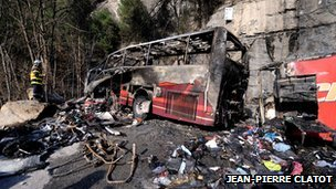 Firefighter stands near bus wreckage