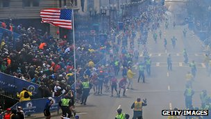 Wide shot of Boston Marathon finish as bomb goes off