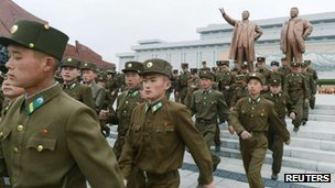 North Korean soldiers visit the bronze statues of North Korea founder Kim Il-sung (L) and late leader Kim Jong-il at Mansudae in Pyongyang, 15 April 2013