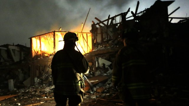 Firefighters use flashlights to search a destroyed apartment