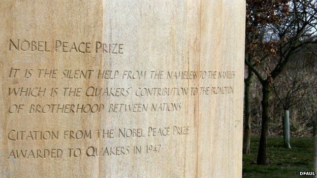 "Close up of one of the benches of the Quaker service memorial. The inscription reads ""It is the silent help from the nameless to the nameless which is the Quakers' contribution to the promotion of brotherhood between nations"", a citation from the Nobel Peace Prize awarded to Quakers in 1947"