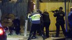 Police officers aim their weapons in Watertown