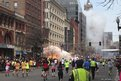 Runners continue to run towards the finish line of the Boston Marathon as an explosion erupts near the finish line of the race