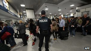 A police officer keeps watch as all trains towards Boston were cancelled at Pennsylvania Station, in New York,