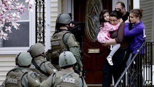 A woman carries a girl from their home as a SWAT team searching for a suspect in the Boston Marathon bombings enters the building