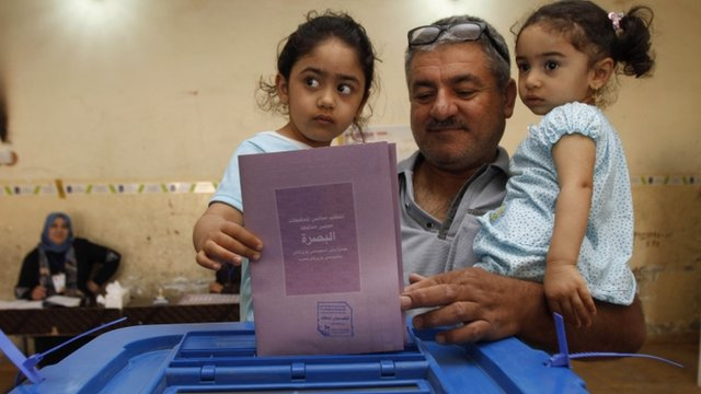 An Iraqi man, holding his two daughters, casts his ballot at a polling station in Basra, Iraq,