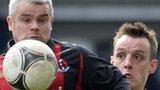 Gary McCutcheon of Crusaders in action against Glentoran's Jason Hill