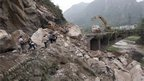 People walk along a damaged road in Baosheng, Lushan, Sichuan province, China (21 April 2013)
