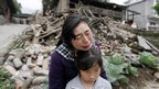 Song Zhengqiong, holding her daughter, cries in front of her damaged house after a strong 6.6 magnitude earthquake at Longmen village, Lushan county
