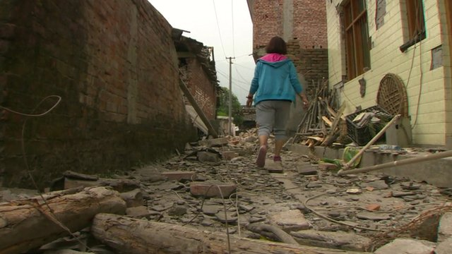 A woman walks through rubble in the village of Longmen