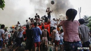 Ethnic Rakhine people get water from a fire truck to extinguish fires during fighting between Buddhist Rakhine and Muslim Rohingya communities in Sittwe, 10 June 2012