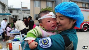 A Chinese medical worker holds an injured child in Longmen, a town close to the epicentre of the earthquake that hit the city in Ya'an, south-west China's Sichuan province, 21 April 2013