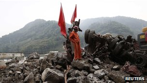 A rescue worker stands beside a truck crushed by a landslide, after Saturday's earthquake, near Lingguan town of Baoxing county, Sichuan province, 22 April 2013