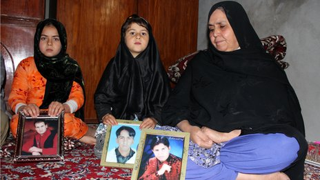 Ruqsana Bibi with photos of her three sons killed by a suicide bomber in Quetta