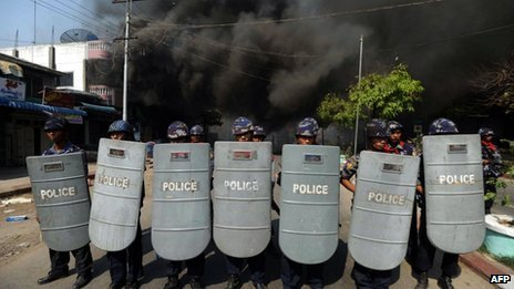 This file picture taken on March 22, 2013 shows policemen forming a line as they block access to part of the town where a house is burning in riot-hit Meiktila, central Myanmar