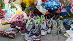 Floral tributes and running shoes lie in memory of those killed and injured at the 2013 Boston Marathon
