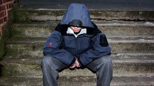 Teenager in hood sits on steps