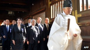 A Shinto priest (R) leads a group of Japanese lawmakers to offer prayers for the country's war dead at the Yasukuni Shrine in Tokyo on the occasion of the shrine's spring festival, 23 April 2013