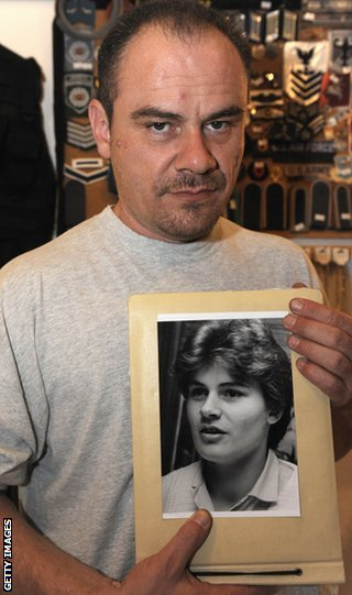 Former German shot putter Andreas Krieger, who competed as a woman (Heidi Krieger) on the East German athletics team, poses with a picture of himself in 1987