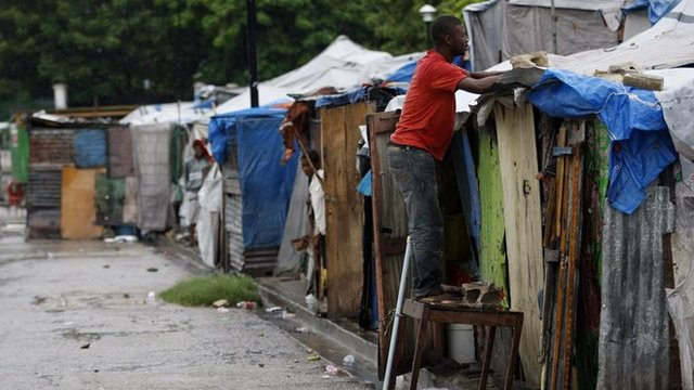 A Haitian earthquake survivor reinforces his tent, under the rain, at a provisional camp