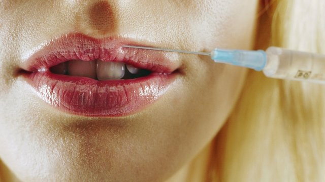 Woman holding collagen needle to her lips