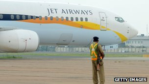 An Indian security official looks on as an aircraft of Jet Airways taxies after landing at Indira Gandhi International Airport in New Delhi