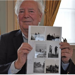 Louis Van Gysel holds up a page of photos of the reunion between his mother and the man who's life she  helped flee down the River Scheldt to Holland