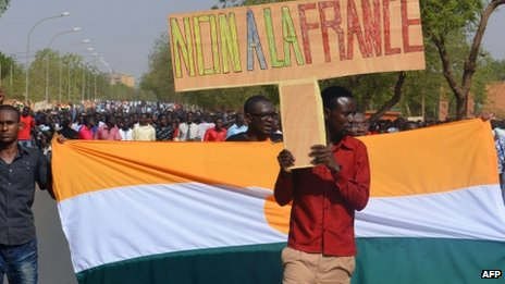 "A student holds a sign reading ""No to France"" as he takes part in a demonstration in Niamey on 5 April 2013 against France and French nuclear energy firm Areva which extracts uranium in the north of Niger"