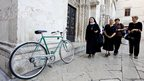 Women and bicycle outside the Cathedral of St Anastasia, Zadar, a picturesque city on Croatia's Adriatic coast.